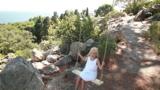 Roztomilý dívka je na houpačce. Dítě je v bílých šatech