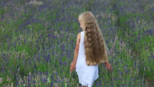 Ragazza carina è in uscita dalla macchina fotografica attraverso il campo. Bambino è in un vestito bianco
