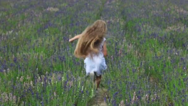 Ragazza carina fuga dalla fotocamera attraverso il campo. Bambino è vestita di bianco. Slow motion
