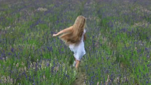 Cute girl escape from camera across the field. Child is in a white dress
