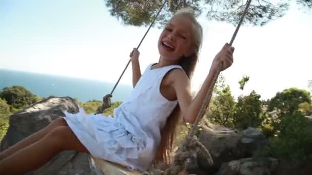 Laughing girl is on a swing. Cute child looking at camera