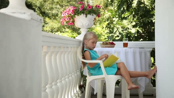 Smiling little girl reading a book in the garden. She hugging the book and looking at camera. Child sitting on a chair at the table. Glass of juice and a basket of grapes are on the table
