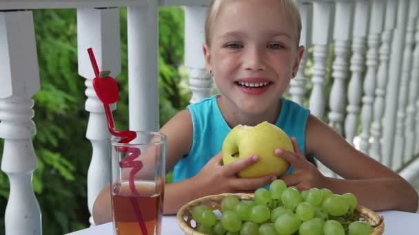 Clouse-up portrét. Dívka u stolu jíst žluté jablko. Na stole je koš hroznové víno a sklenice jablečného džusu. Palec nahoru. Ok