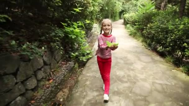 Girl walking on the path in the park and holding a paper toy ship. Schoolgirl launches a paper boat in a stream