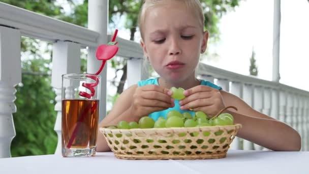 Dítě jíst hrozny a usmívá se na kameru. Dívka má ráda hrozny