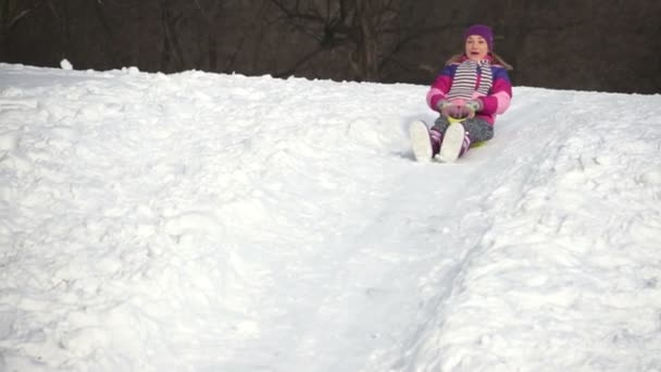 Beautiful woman riding on a sled down the hills. Slow motion
