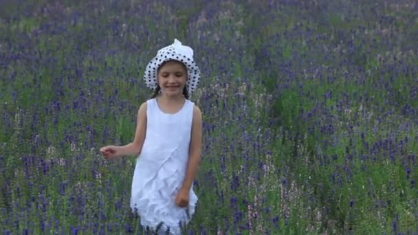 Girl in the white hat is walking on the field of purple flowers. Child looking at camera