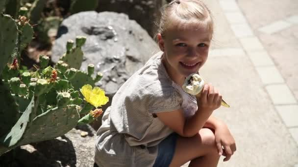Happy little girl eats ice cream in hot weather and shows class. Thumbs up. A child sits near a cactus