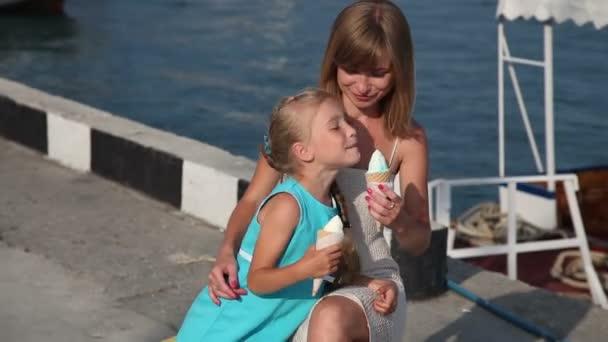 Matka a dcera jíst zmrzlinu. A dcera dabbles. Rodiny při pohledu na fotoaparát a usmívá se