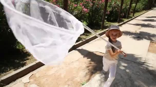Happy little girl catching a camcorder in the net for butterflies. Girl caught the butterfly