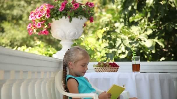 Peuter meisje het lezen van een boek in de tuin kind aanbrengen