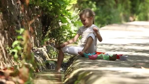Mädchen, das neben einem Bach sitzt und viele Papierboote auf dem Wasser startet und klatscht