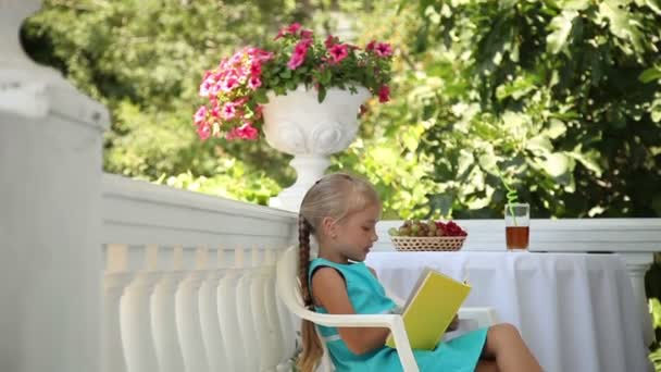 Preschooler girl reading a book in the garden. Child siting on a chair at the table. Glass of juice and a basket of grapes are on the table