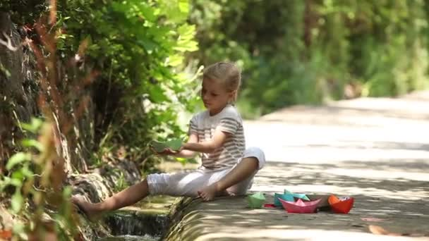 Child playing with toy ship near a brook