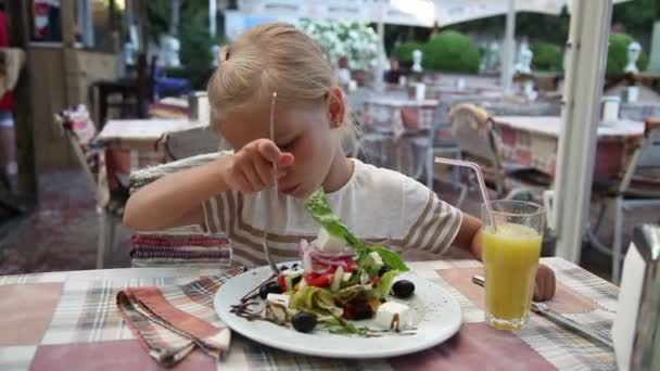 Little girl eating a Greek salad in the cafe and looking at the camera