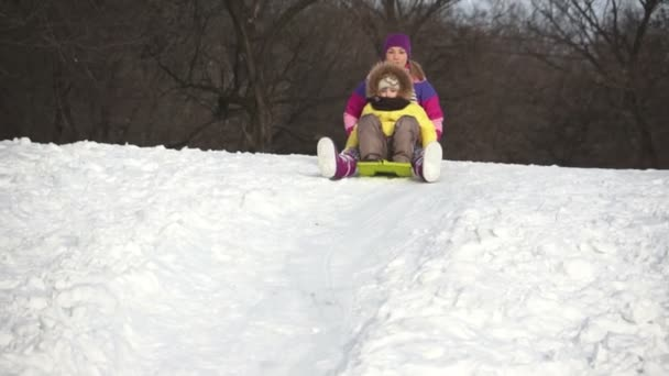Mother and doughter riding on a sled down the hills