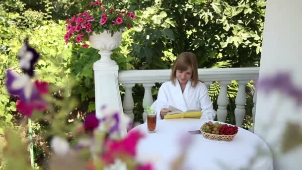 Woman reading a book and smiling at the camera. Young adult sitting at the table. Fruits are on the table