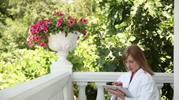 Young adult in a bathrobe with a tablet PC. Woman is On-line