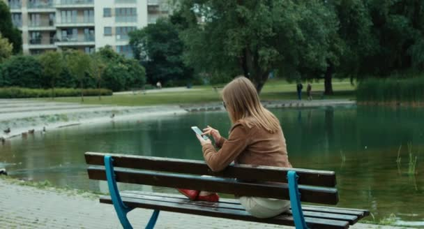 Young adult woman sitting on the bench in the park and using cell phone