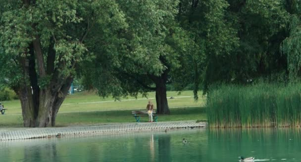 Young adult woman resting in the park and reading a book. Woman is sitting on bench near the pond