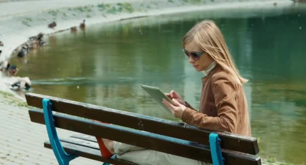 Portrait young adult woman using tablet pc and sitting on the bench