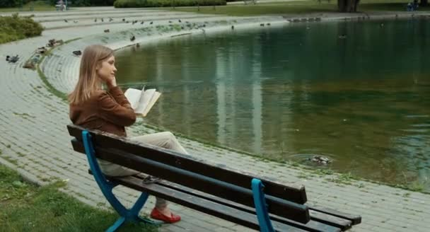 Young adult woman reading a book. Woman sitting on a bench in the park and smiling at camera