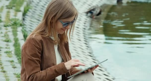 Closeup profile of young adult woman using tablet pc and sitting on the ground against the backdrop of the pond