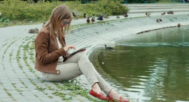 oung adult woman using tablet pc and sitting on ground against the backdrop of the pond