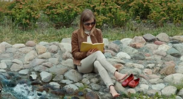 Young adult woman resting in the park and reading a book
