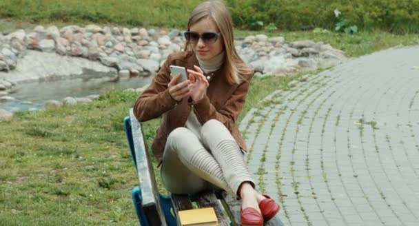 Young adult woman sitting on the bench and using cell phone in the park