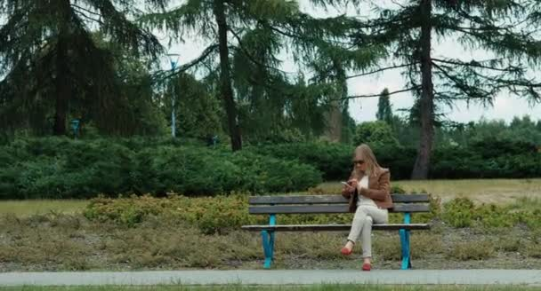 Young adult woman in the park using cell phone and sitting on the bench. Wide angle