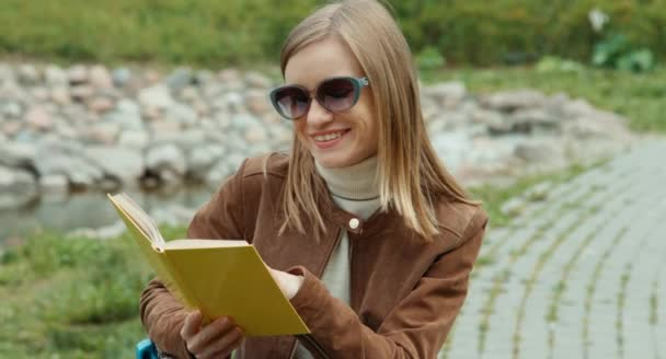 Portrait young adult woman reading a book in the park and smiling at camera