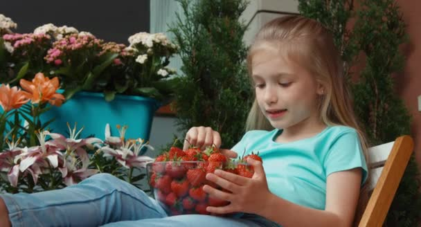 Girl holding a huge plate of strawberries and eating it