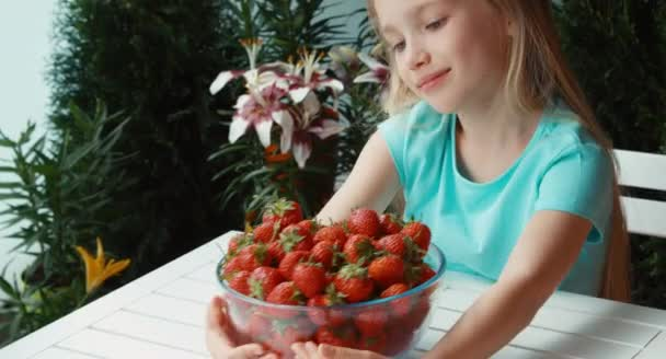 Girl with a big plate of strawberries looking at camera. Thumbs up. Ok