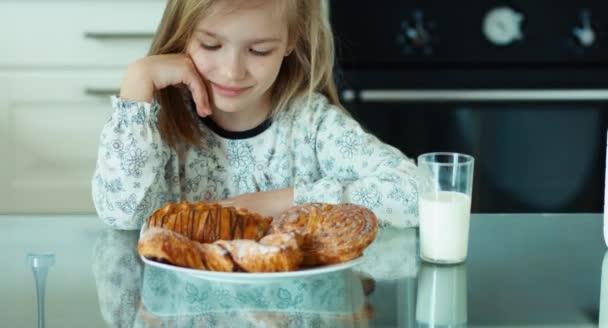 Portrét dívky obdivným sladké rohlíky. Dívka mrknutí. Palec nahoru. Ok