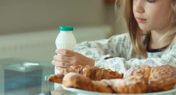 Girl drinking yogurt and looking at camera. Thumb up. Ok