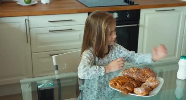 Dítě má snídaně, dívka otevírá lahev jogurt