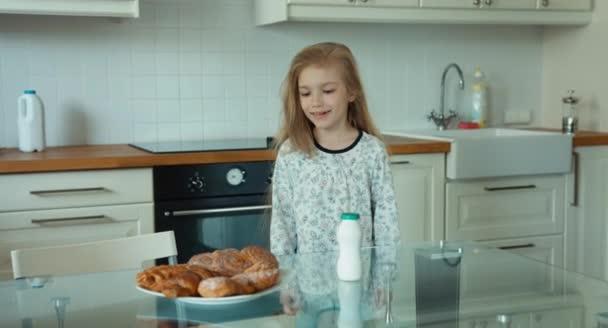 Dívka ráno v kuchyni. Dítě se protahuje sám. Palec nahoru. Ok