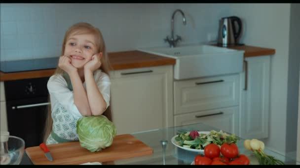 Dívka šéfkuchař v kuchyni, při pohledu na fotoaparát a usmívá se. Palec nahoru. Ok. Zvětšení/zmenšení