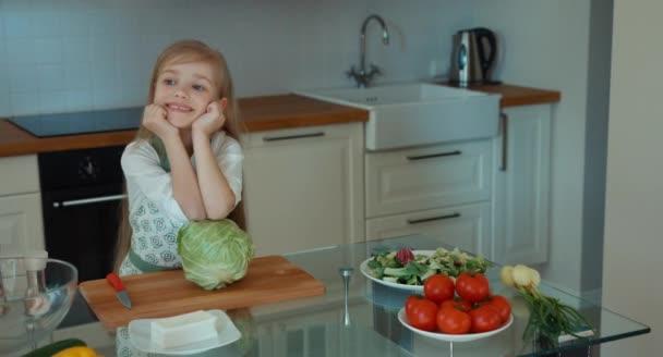 Dívka šéfkuchař v kuchyni, při pohledu na fotoaparát a usmívá se. Palec nahoru. Ok