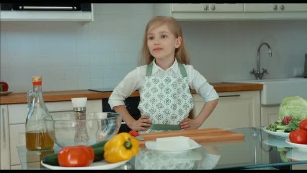 Usmívající se dívka šéfkuchař v kuchyni, při pohledu na fotoaparát. Dítě drží za ruce na opasku. Palec nahoru. Ok. Zvětšení/zmenšení