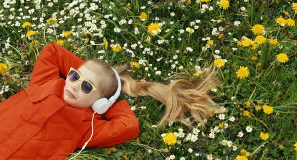 Detailní portrét smějící se dívka poslechu hudby. Dítě ležící na trávě mezi květy. Palec nahoru. Ok