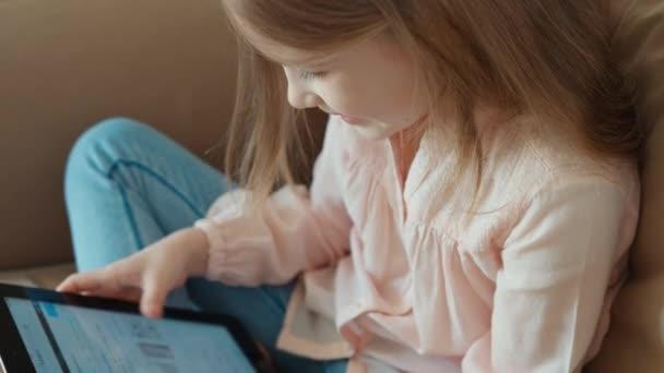 Blondýna Detailní záběr, Holčička je online s tablet pc a sedí na gauči. Dítě s úsměvem a zívá