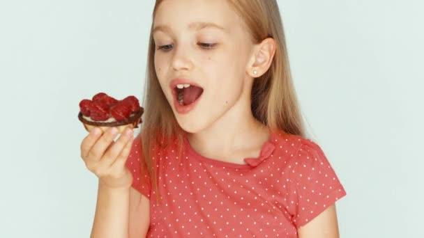 Mädchen isst einen Kuchen mit Himbeeren auf weißem Hintergrund. Nahaufnahme