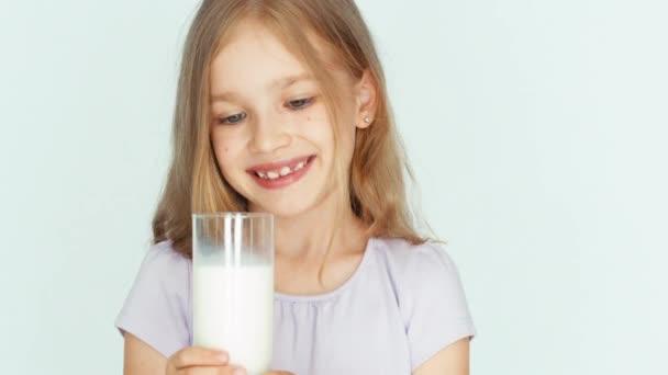 Konzumní mléko dítě. Dívka ukazuje sklenici mléka na kameru. Dívka s krásnou blond vlasy na bílém pozadí. Velké oči. Closeup