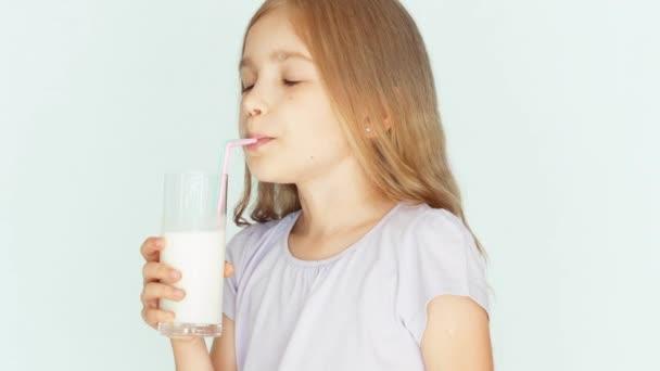 Šťastné dítě pít mléko. Dívka s krásnou blond vlasy na bílém pozadí. Palec nahoru. Ok. Closeup