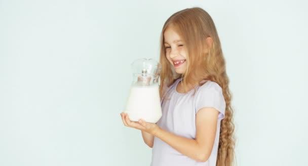 Dítě čichání mléko. Dítě zobrazeno džbán mléka na kameru. Dívka s krásnou blond vlasy na bílém pozadí. Palec nahoru. Ok