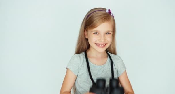 Lány keres keresztül távcső kamerát egy fehér háttér