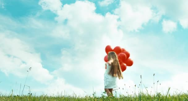 Girl with red balloons spinning at camera