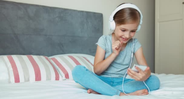 Child girl sitting on the bed and listening music in headphones from smartphone cell phone and dancing